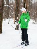 摆在一件的高尔夫球外套的女孩,当滑雪在冬天森林里时 免版税库存照片