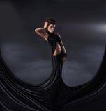 摆在一件黑暗的礼服的一名新深色的妇女 图库摄影