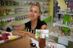 摆在一位年轻迷人的成功的妇女的企业家的画象,当站立在她的化妆商店内部时, 免版税库存照片