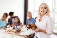摆在一台照相机前面的一名中年妇女用一只被烘烤的火鸡 图库摄影