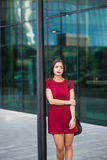 摆在一名年轻迷人的女实业家的画象,当单独站立在现代办公楼附近时, 免版税库存照片