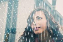 摆在一块残破的玻璃后的美丽的女孩 库存图片