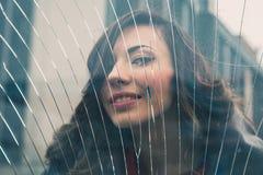 摆在一块残破的玻璃后的美丽的女孩 免版税库存照片