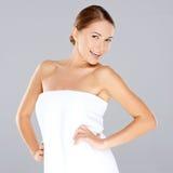 摆在一块白色毛巾的微笑的妇女 图库摄影