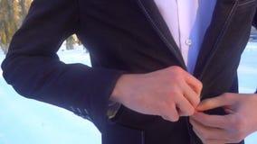 摆在一套无尾礼服的年轻人在冬天反对白色雪 股票视频