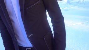 摆在一套无尾礼服的年轻人在冬天反对白色雪 影视素材