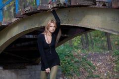 摆在一座步行桥下的美丽的女孩 免版税库存照片