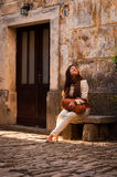 一名逗人喜爱的妇女坐在老地中海st的一条石长凳 图库摄影