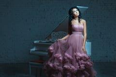 摆在一架白色钢琴旁边的美丽的妇女 库存图片