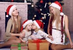 摆在一棵装饰的圣诞树旁边的愉快的家庭 库存图片