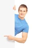 摆在一白色盘区和指向后的一个微笑的英俊的男性 免版税库存图片