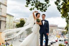 摆在一种伟大的都市风景的前面的新娘和新郎微笑 库存图片