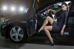 摆在一辆花梢黑汽车的时装模特儿 免版税库存照片