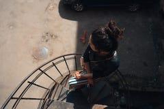 摆在一部螺旋形楼梯的女孩 免版税图库摄影