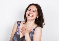摆在一件五颜六色的礼服的美丽的年轻深色的妇女和表现出不同的情感 喜悦,笑 特写镜头portret 免版税图库摄影