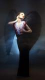 摆在下落的天使的类似性感的女子 免版税图库摄影