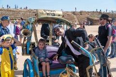 摆在与一个访客的普珥节节日的参加者在凯瑟里雅,以色列 免版税库存图片