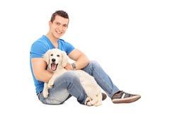 摆在与一只逗人喜爱的小的小狗的快乐的年轻人 免版税库存照片