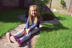 摆在与一张逗人喜爱的面孔的女孩 获得在庭院的乐趣 使用愉快的小孩的女孩外面 库存图片