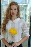 摆在与一朵黄色花的女孩 库存图片