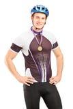 摆在与一枚金黄奖牌的满足的男性骑自行车者赢利地区 免版税库存图片
