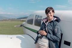 摆在与一架小型飞机的摄影师 免版税库存图片