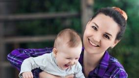 摆在与一点笑的小孩子的愉快的年轻母亲的特写镜头面孔看照相机 股票录像