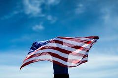 摆在与一面美国国旗的运动员背面图的综合图象 图库摄影