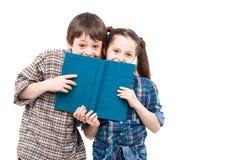 摆在与书的兄弟和姐妹 免版税库存图片