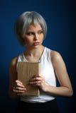摆在与书的银色假发的女孩 关闭 背景看板卡祝贺邀请 免版税图库摄影