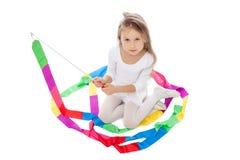 摆在与五颜六色的丝带的可爱的小女孩 库存图片