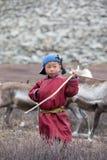 摆在与他的家庭` s驯鹿的小tsaatan男孩 库存照片