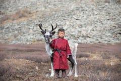 摆在与他的家庭` s驯鹿的小tsaatan男孩 库存图片