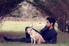 摆在与他的狗的英俊的人本质上 免版税库存照片