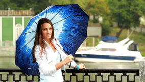 摆在与伞的美丽的女孩。 影视素材