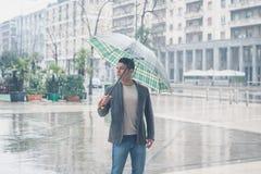摆在与伞的年轻英俊的人 免版税库存图片