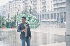 摆在与伞的年轻英俊的人 免版税库存照片