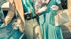 摆在与减速火箭的衣裳下辆经典汽车的葡萄酒夫妇 免版税图库摄影