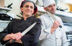 摆在与刀子的厨师在他们的餐馆厨房里 免版税库存照片