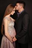 摆在与华美的孕妇的英俊的人 库存图片