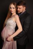 摆在与华美的孕妇的英俊的人 免版税库存图片