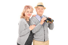 摆在与双筒望远镜的成熟夫妇 免版税库存照片