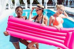 摆在与可膨胀的床垫的愉快的不同种族的妇女在游泳池附近 免版税库存照片