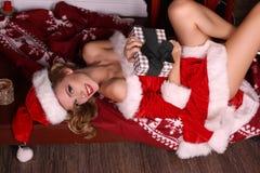 摆在与圣诞节礼物的圣诞老人服装的性感的白肤金发的女孩 免版税库存图片