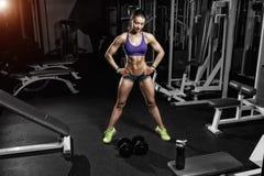 摆在与在健身房的一个哑铃的性感的运动员妇女 免版税库存图片