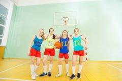 摆在与在健身房的篮球的愉快的十几岁的女孩 免版税库存照片