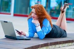 摆在与在办公楼前面的一台膝上型计算机的女商人  免版税库存照片