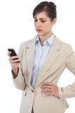 摆在与在右手的电话的严肃的女实业家 库存图片