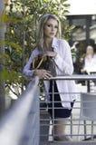 摆在与在城市场面的提包的美丽的白肤金发的都市妇女 免版税库存照片