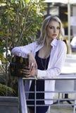 摆在与在城市场面的提包的迷人的白肤金发的都市妇女 库存照片